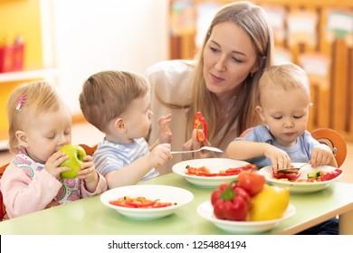 teacher and preschooler kids having break for fruits and vegetables in kindergarten