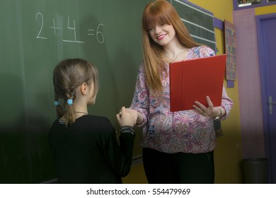 The teacher and the pupil in front of the table