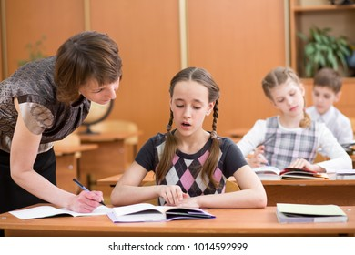 Teacher and pupils in classroom learning together. School child boy looks together with teacher in book.