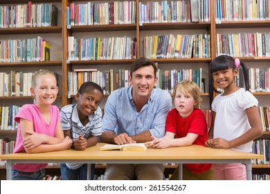 Teacher and pupils smiling at camera at library at elementary school