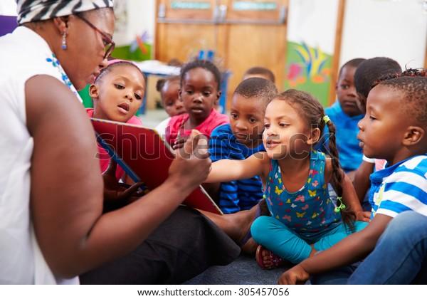 Enseignant lisant un livre avec une classe d'enfants d'âge préscolaire