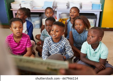 Teacher reading book to elementary school children in class