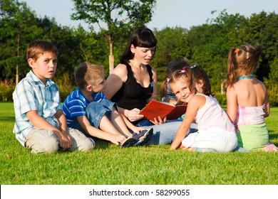 Teacher reading book to preschool kids