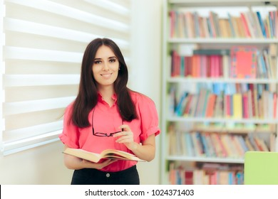 Teacher Reading a Book in a School Library. Female professor holding a text book and her eyeglasses
