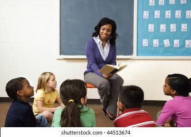 Lehrer, der jungen Schülern im Klassenzimmer Buch liest. Horizontal gerahmte Aufnahme.