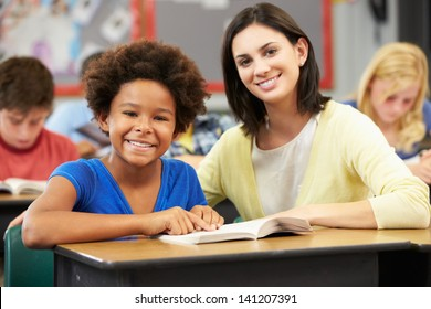 Teacher Reading With Female Pupil In Class