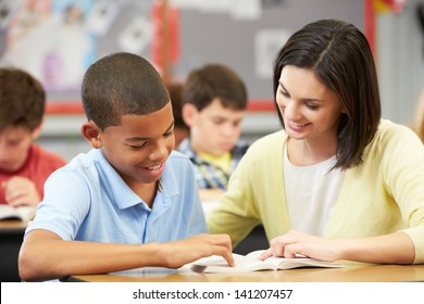 Teacher Reading With Male Pupil In Class