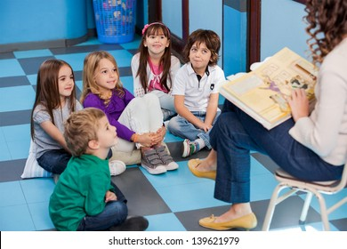 Teacher reading story book to children in kindergarten