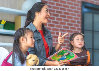 Teacher is reading story book to kindergarten students pointing
