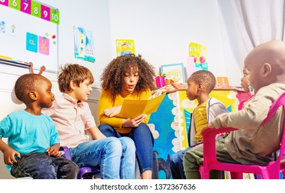 Teacher reads a book to group of kids in nursery