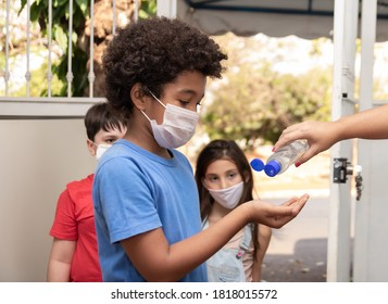 Teacher sanitizing children's hands with alcohol gel in return to classes after quarantine. Student passing alcohol in gel and wearing protective mask. Hygiene concept against covid
