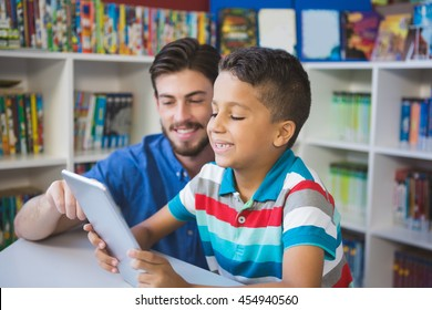 Teacher and school kid using digital table in library at school