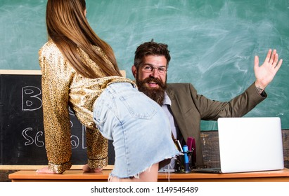 Teacher or school principal punishes slapping buttocks sexy girl student. Student in mini skirt with sexy buttocks waits for punishment. Role game concept. School behaviour discipline and punishment.