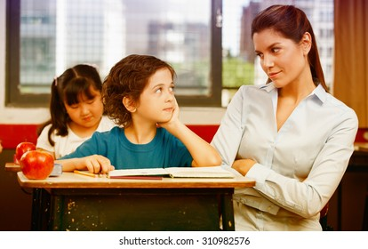 Teacher and schoolboy looking each other in primary classroom.
