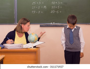 The teacher scolds a little schoolboy in a classroom.