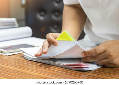 Teacher is searching for homework assignment documents of student on the teacher's desk. Paperwork pile print document organized put on the table.