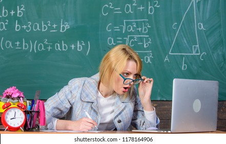 Teacher shocked face keep working after classes. Teacher woman sit table classroom chalkboard background. Still working. Teacher busy with paperwork and research. Work far beyond actual school day.