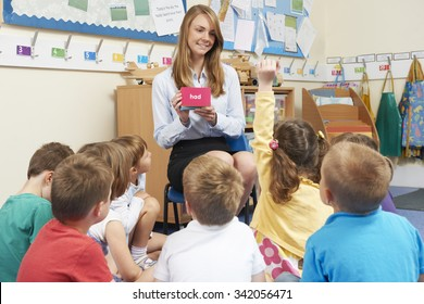 Teacher Showing Flash Cards To Elementary School Class