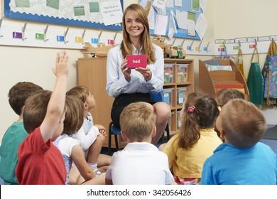 Teacher Showing Flashcard To Elementary School Class