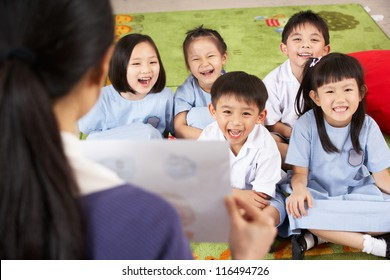 Teacher Showing Painting To Students In Chinese School Classroom