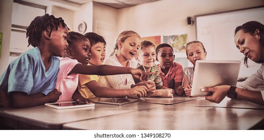 Teacher showing tablet computer to students in classroom at office