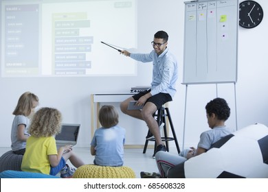 Teacher shows students how to program on an interactive whiteboard. Modern teaching concept