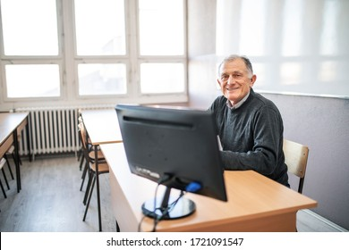 Teacher sitting in the classroom, and uses a computer