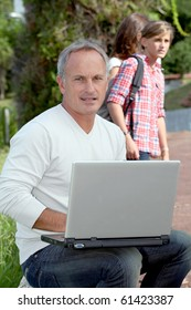 Teacher sitting outside with laptop computer