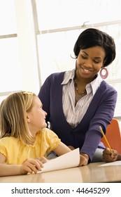 Lehrer lächeln und helfen Schülern mit Schularbeit in der Schule. Vertikal gerahmte Aufnahme.