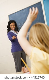 Teacher smiling and pointing to student with hand raised. Vertically framed shot.