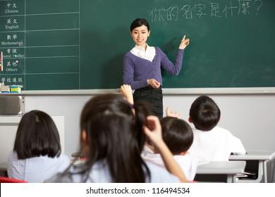 Teacher Standing By Blackboard In Chinese School Classroom