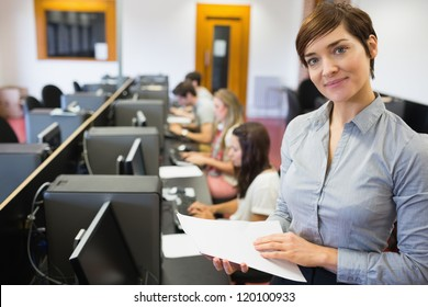Teacher standing at the computer room holding papers in college