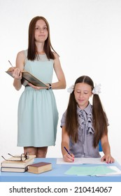 Teacher standing at desk behind which sits a diligent student