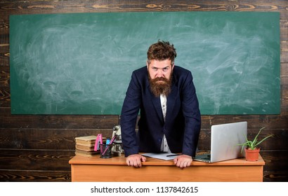 Teacher strict serious bearded man lean on table chalkboard background. Teacher looks threatening. School principal threatening with punishment. Rules of school behaviour. Man unhappy with behaviour.