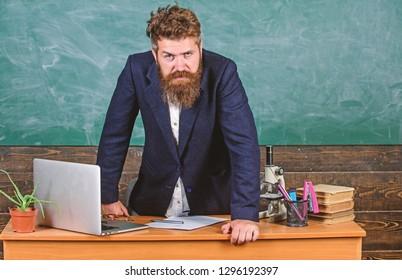 Teacher strict serious bearded man lean on table chalkboard background. Teacher looks threatening. Rules of school behaviour. Man unhappy with behaviour. School principal threatening with punishment.