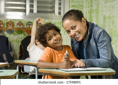 A teacher with a student in a classroom.  They are facing the camera and are smiling. Horizontally framed shot.