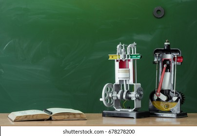 Teacher, student or engineer desk table. Education background. Education concept. Open book textbook and education models of internal combustion engine on the table.