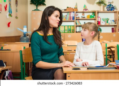 teacher with a student at a school desk