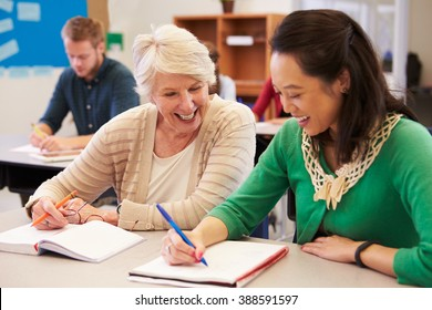 Teacher and student sit together at an adult education class