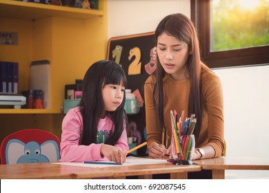 Teacher and student take home work together in preschool, Library, mother, art, school, teacher, education and kid concept