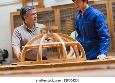 Teacher and student at a workbench in a woodworking class talking about a frame