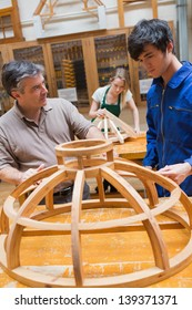 Teacher and student at a workbench in a woodworking class working on a frame
