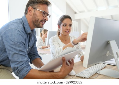 Teacher with student working on computer