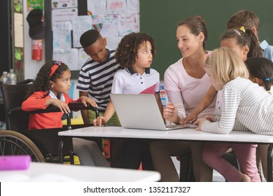 Teacher and students discussing over laptop in classroom at school