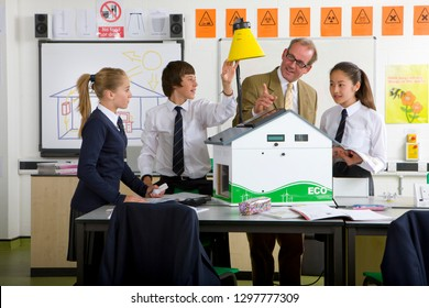 Teacher and students with eco house model studying alternative energy