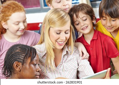 Teacher and students looking at tablet computer in elementary school class