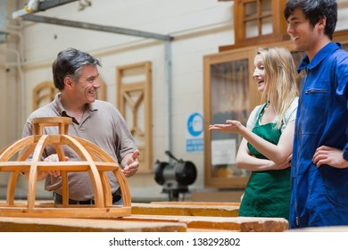 Teacher and students standing in a woodwork class and having fun