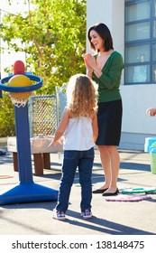 Teacher Supervising Breaktime At Elementary School
