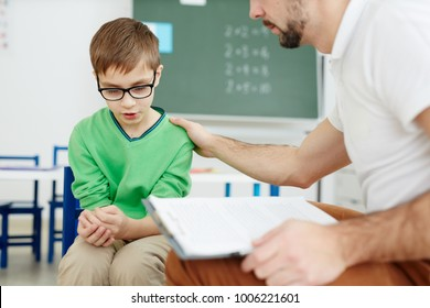 Teacher supporting upset or confused schoolboy during individual lesson