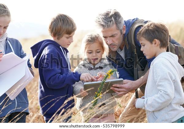 Profesora llevando a los niños al campo para explorar plantas y flores